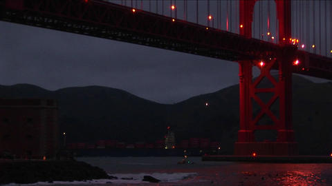 Small boats passing under the Golden Gate Bridge at night are dwarfed by the enormous structure Footage
