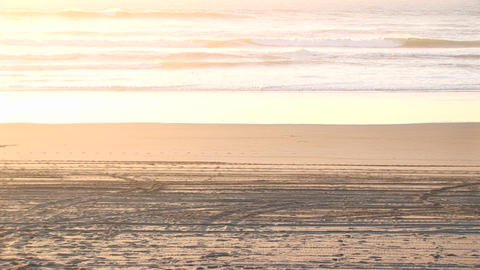 A dirtbiker pops a wheelie on a sandy beach with no one... Stock Video Footage