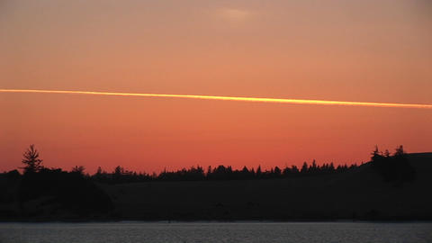 Long-shot of the vapor trail from a jet makes a colorful streak across the golden-hour sky Live Action