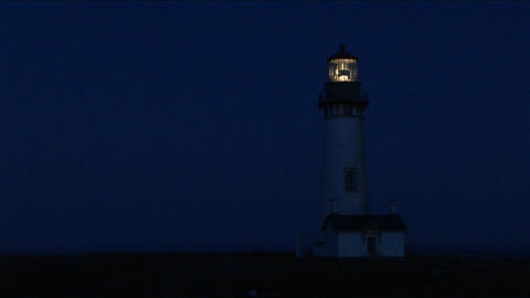 A lighthouse at night with its flashing light Footage