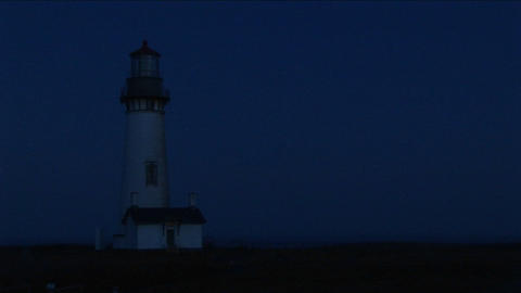 Medium shot of lighthouse at night with its bright beacon signaling a warning to passing ships Footage