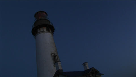 A worms-eye view of a lighthouse tower and beacon at night Footage