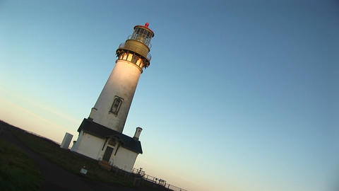 The camera takes an angled shot of this lighthouse on a sunny day Live Action