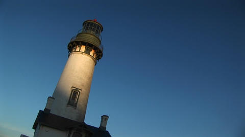 A hand-held, jaunty view of a lighthouse with sunlight on its white tower Footage