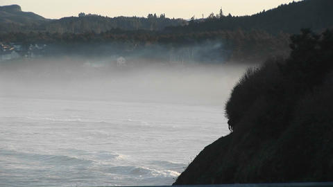 Long-shot of ground fog as the ocean waves roll in on the... Stock Video Footage