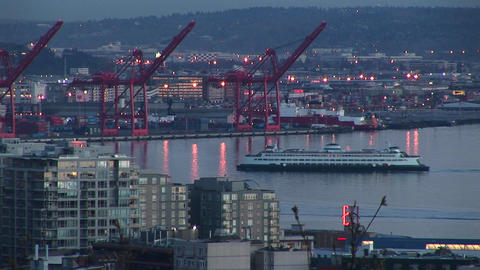 A cruise ship makes its way through Seattle's harbor surrounded by warehouses, drydocks and building Footage