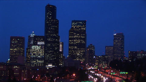 Long shot of a group of Seattle's skyscrapers towering above an inner-city expressway Footage