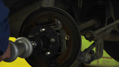 A mechanic tightens bolts on a wheel being fastened to an... Stock Video Footage