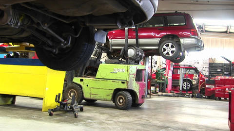 An auto repair shop with cars on lifts and mechanics... Stock Video Footage