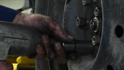 A mechanic tightens lug-nuts with a power tool in this... Stock Video Footage