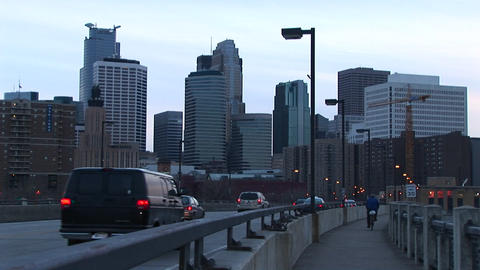 Cars and a bicyclist cross a bridge into the city Stock Video Footage