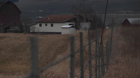 The camera looks over a fence to a rural farm in early winter Footage