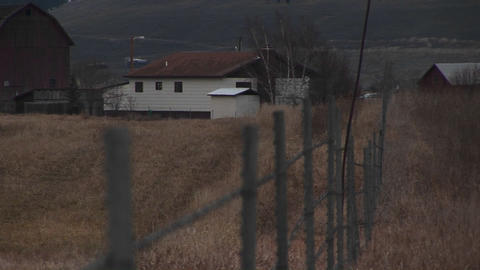 The camera looks over a fence to a rural farm in early... Stock Video Footage