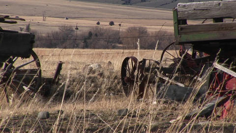 Broken And Abandoned Farm Machinery Rest In A Field That Overlooks The Dry Prairie Beyond stock footage