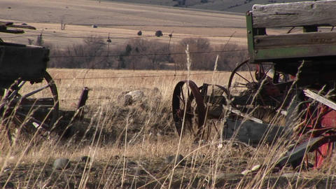 Broken and abandoned farm machinery rest in a field that... Stock Video Footage