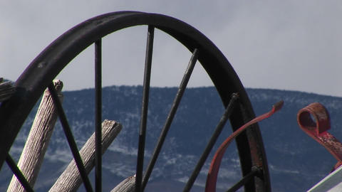 Camera looks at mountains through the spokes of abandoned wagon wheels Live Action