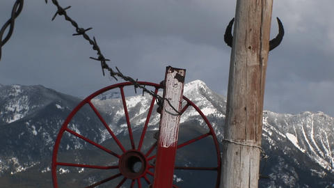 Medium shot of western mountains, red wagon-wheel rim, barbed-wire and cattle horns tacked to a pole Footage