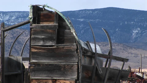 The remains of an old sheep wagon are featured in front of the mountains in the background Footage