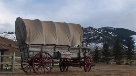 A covered wagon is featured front and center with snow-dusted mountains in the background Footage