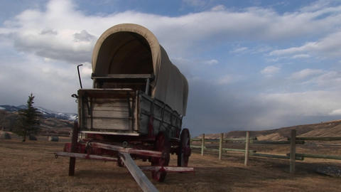 Only a split-rail fence separates a historic covered-wagon from a modern-day day road traveled by ca Footage