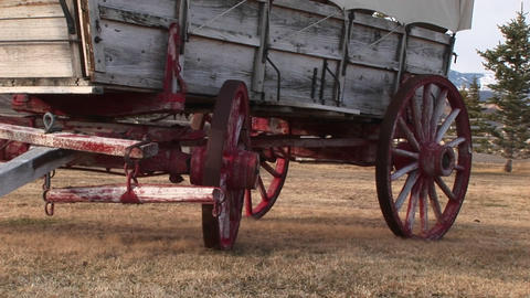 A close look at the lower half of a covered wagon with its wagon wheels painted red Footage
