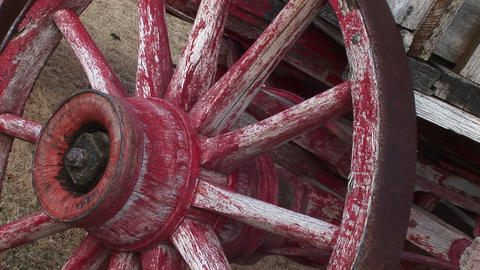 A worn covered wagon wheel shows the remains of its original red paint Footage