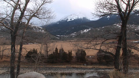 A dry winter prairie is bordered by foothills and mountains in the background Footage
