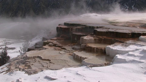 Steam rises from this hot springs terrace covered with snow Stock Video Footage