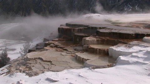Steam rises from this hot springs terrace covered with snow Footage