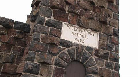"Camera focuses on a vintage Yellowstone National Park"" sign embedded in the brick facade of an old b Footage"