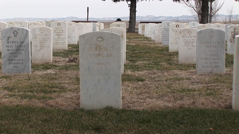 The camera pans an old military cemetery with white headstones arranged in precise rows Footage