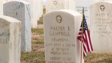 An American flag decorates the headstone of a fallen hero... Stock Video Footage