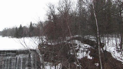 The camera pans left from a rural winter landscape to dam... Stock Video Footage