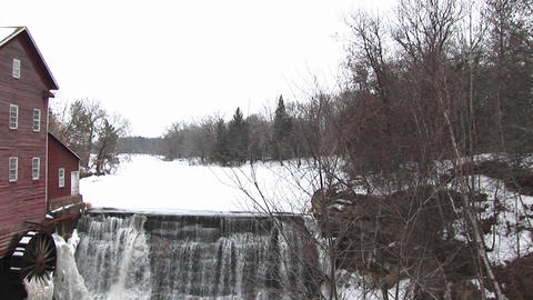 The camera pans left from a rural winter landscape to dam next to a mill with waterwheel Footage