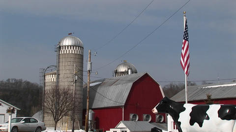 The camera captures an American farm with silos, red barn, American flag and life-size replica of a Footage