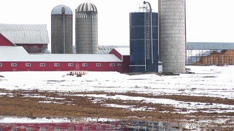 A puddle of melting snow reflects farm buildings and silos in the background Footage