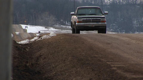 Camera placed in roadside ditch along a rural two-lane road captures a pickup truck coming into view Footage