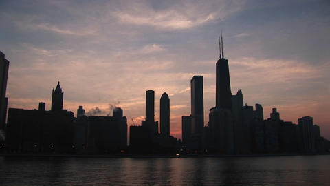 The beautiful Chicago skyline is silhouetted at sunset Stock Video Footage