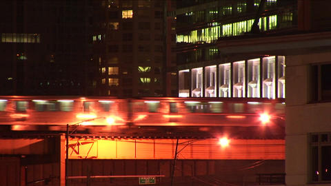 An elevated train moves through the city at night Footage