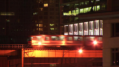 An elevated train moves through the city at night Stock Video Footage