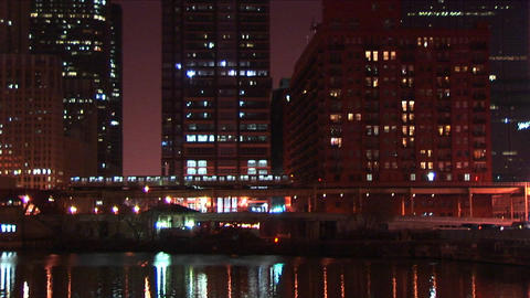 An elevated commuter train moves slowly through downtown Chicago at night Footage