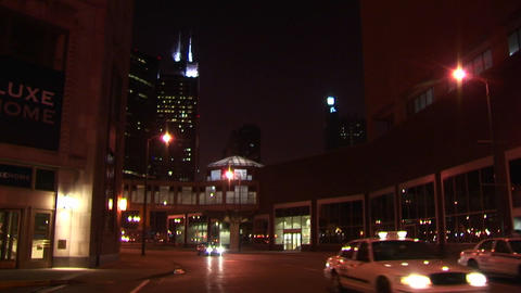 Nighttime urban scene with taxis and other vehicles traveling across an intersection with Chicago l Footage