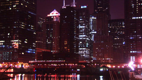 Chicago's buildings sparkle at night as a commuter train moves across the city Live Action