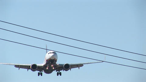 An airplane flies over power lines with its landing gear... Stock Video Footage