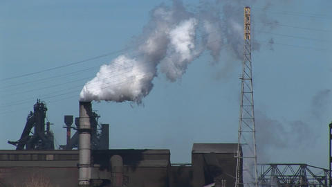 Smoke billows out of an industrial building's smokestack Footage