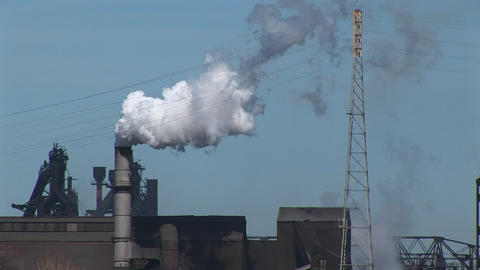 Smoke billows out of an industrial building's smokestack Stock Video Footage