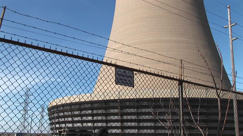 The camera pans from the base of a nuclear power plant to the top of its curved structure Footage