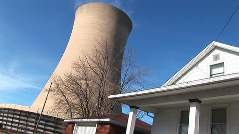 The huge cone of a nuclear power plant looms above a home Stock Video Footage