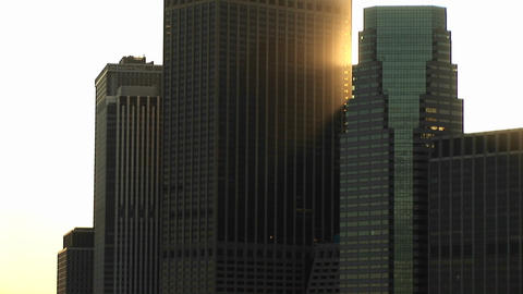 Impressive skyscrapers as seen from the river skyward with sunlight catching the corner of one build Footage