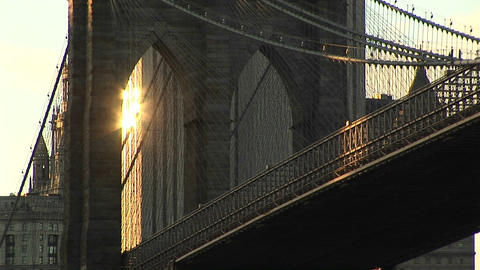 The Brooklyn Bridge's gothic-arches just catch the reflected light from a building in the distance Footage